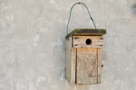 a wooden bird house hanging on a cement wall 写真素材 - 98002266