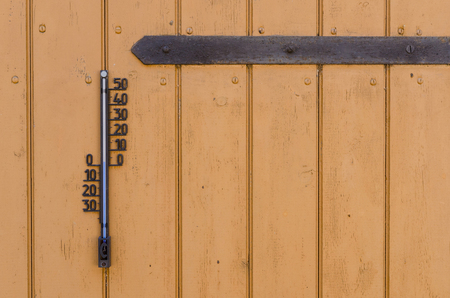 an old outdoor thermometer hanging on a wooden door with a rusty metal hinge showing cold temperature 写真素材 - 98054031
