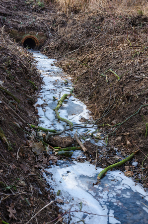 frozen stream leading to the stone drain in the forest in winter 写真素材