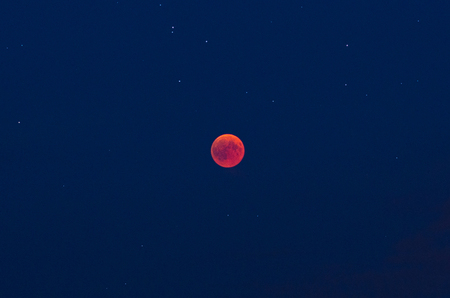 Total lunar eclipse   with red moon and stars and the blue sky 写真素材