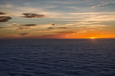 sun setting in the sea of clouds with beautiful and colorful sky above