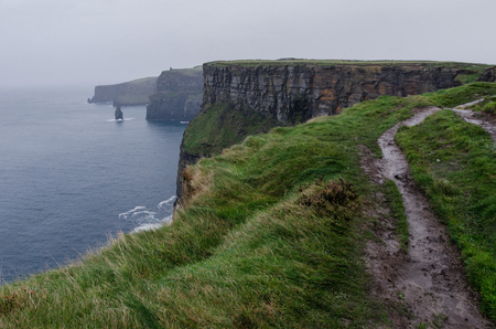 path in the grass atop the cliffs of moher in Ireland on a hazy and rainy day 写真素材