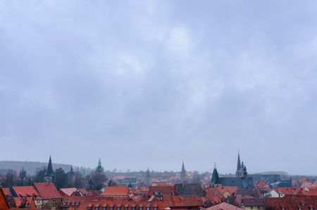 Panorama of the old town of Quedlinburg in Germany with its many half-timbered historic houses, churches and towers under a cloudy sky on a foggy rainy day