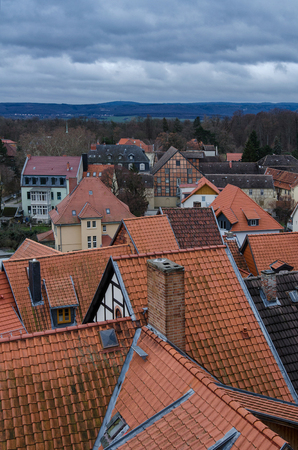 View over the rooftops of half-timbered houses in the old town of Quedlinburg to the Harz mountain range under a cloudy evening sky