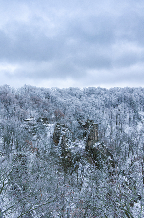 Rock formations in stark contrast to the snow covered forest ner the Hexentanzplatz in the Harz mountains