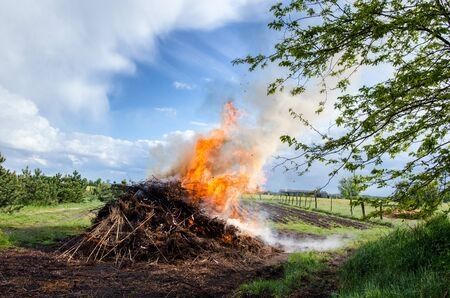 large rural bonfire in the countryside burning near nature on a beautiful spring day