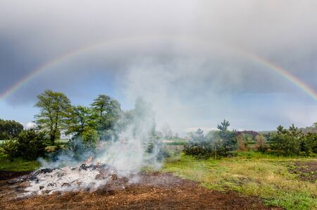 smoke from a large rural bonfire in the countryside slowly rising into the clouds filled sky with a beautiful rainbow during slight rain