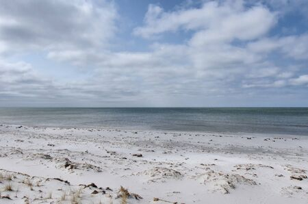 Sand beach at the coast of Baltic sea under cloudy sky