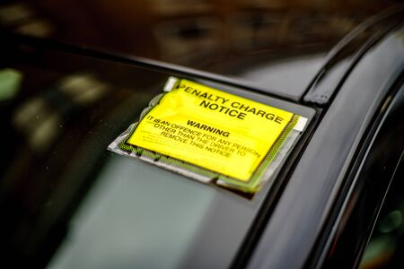 Coventry, UK - August 27, 2018: Generic penalty charge notice (parking fine) attached to windscreen of white car parked on street in Coventry, UK Editoriali
