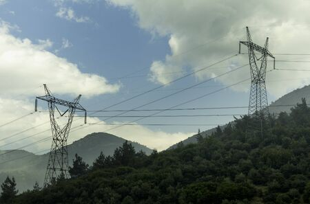 Electricity pylons cutting through forest. Electric power lines at Mountain