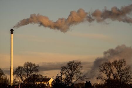 polution coming from chimney of power plant at sunrice Stock Photo