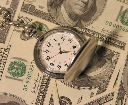 A photo of a pocket watch on hundred dollar bills