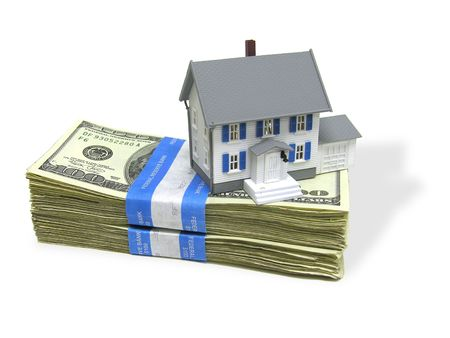 A home on a stack of cash, signifying home buying