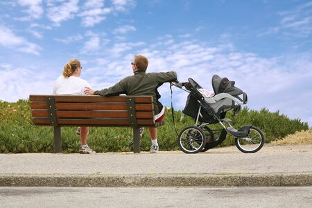 mother on bench: Mom and dad relaxing on a bench watching  Stock Photo