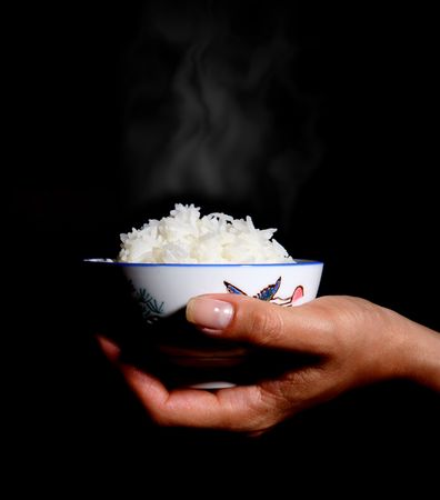 Asian woman holding a bowl of steaming rice