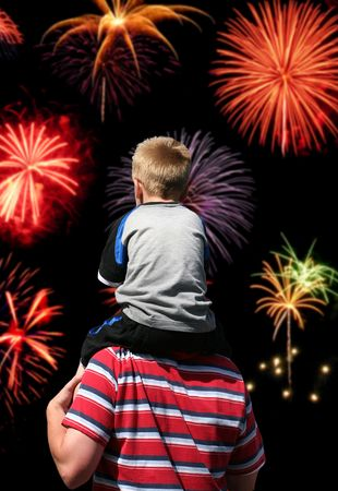 july: A boy on his fathers back watching the fireworks