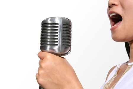 harmonize: Woman singing into a microphone (Focus on Microphone) Stock Photo