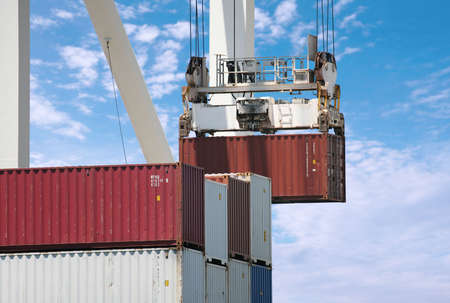 Crane loading a cargo container at port