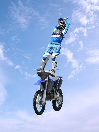 A stunt rider doing tricks on his dirt bike photo