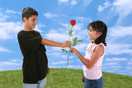Young boy giving a young girl a red rose photo