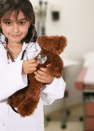 yong: A yong girl playing doctor with her teddy bear Stock Photo
