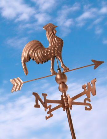 Weather vane in the blue sky