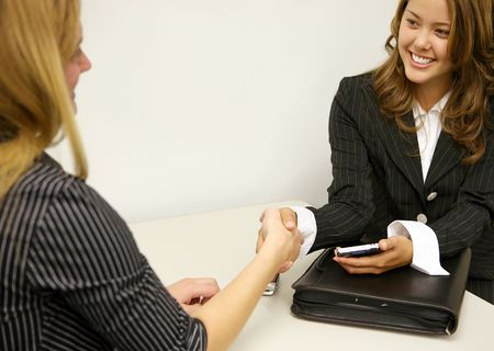 concluding: A business deal between two women concluding with a handshake
