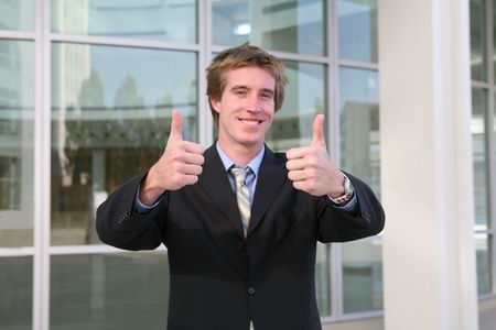 success focus: A business man with his thumbs up indicating success (Focus on Thumbs)