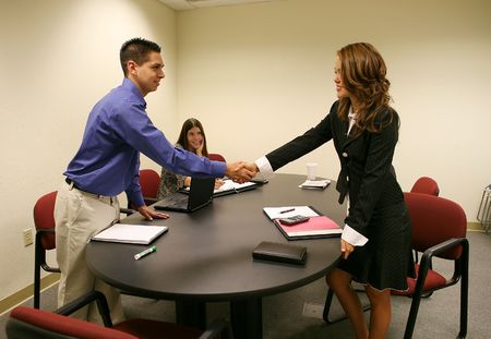 conclude: A woman shaking a mans hand to conclude a business deal