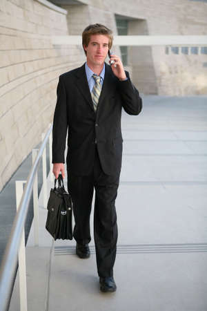 A business man walking to work talking on the phone Stock Photo - 603439