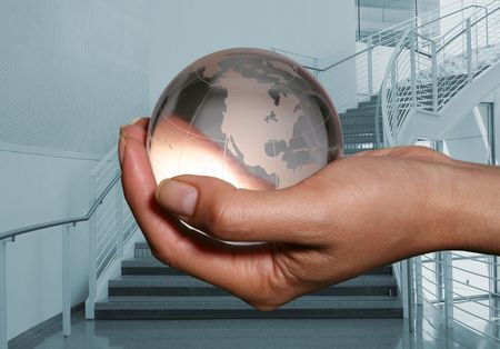 Woman holding glass globe with a building interior in the background photo