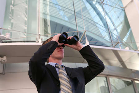 A business man looking into binoculars at his company photo