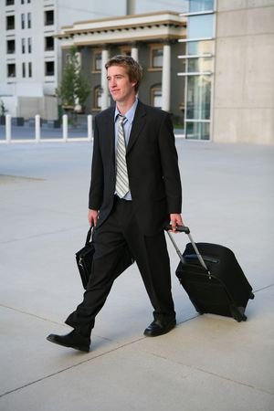 lug: A business man carrying a briefcase a pulling a suitcase travelling