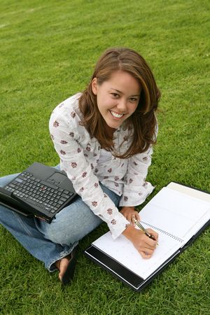 dayplanner: A woman sitting on the grass with her laptop and writing in a notebook