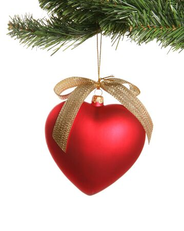 A heart ornament hanging from a Christmas tree Stock Photo