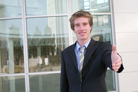 A business man offering a handshake outisde a office building Stock Photo - 648109