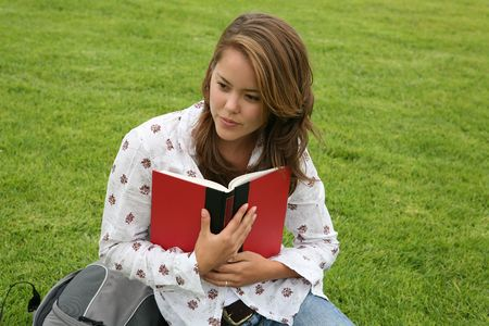A pretty young woman reading a book on the college campus photo