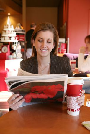 hot secretary: A business woman taking a coffee break and reading the newspaper