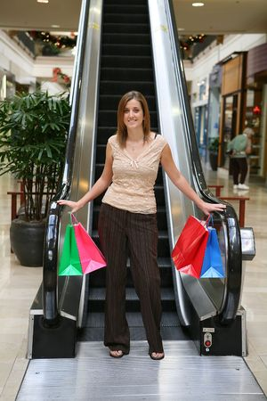 A pretty woman coming down the escalator with shopping bags in hand photo