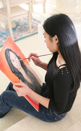 A young woman painting a self  portrait (Focus on Painter) photo