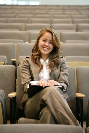 femal: A beautiful business woman sitting alone in an auditorium