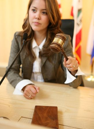 A judge in a courtroom striking the gavel (Focus on Gavel) photo
