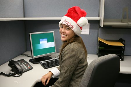 A woman wearing a Santa hat in the office photo