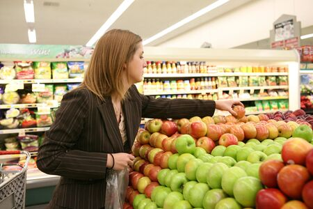 A woman in the grocery store selecting an apple