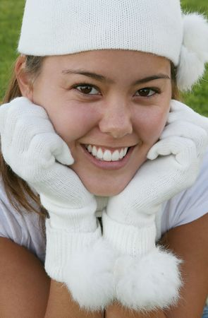 A beautiful young woman in gloves and cap with a pretty smile