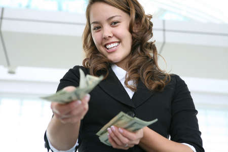 A pretty business woman handing some money Imagens
