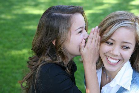 Two teenage women telling secrets in the park Stock Photo - 697849
