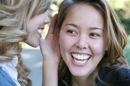 Two teenage women telling secrets in the park Stock Photo - 697854