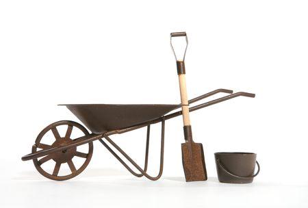 old wood farm wagon: A rusty wheelbarrow, shovel and pail over white Stock Photo