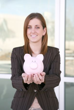 accrue: A pretty business holding a piggy bank (focus on piggy bank) Stock Photo